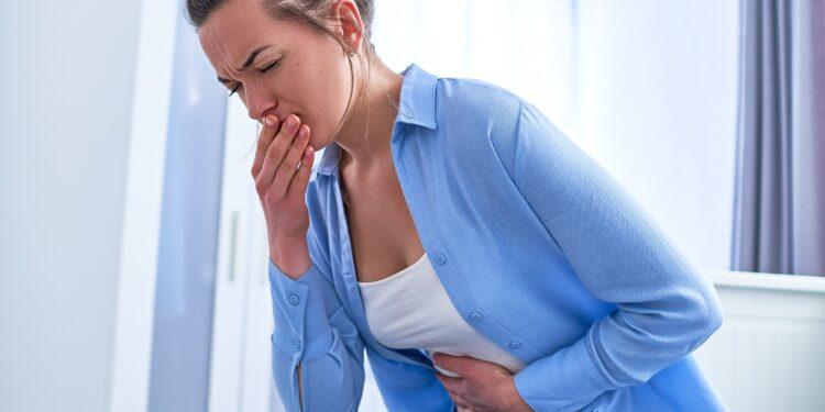 Sitzende Frau mit schmerzverzerrtem Gesicht hält sich ihre Hände an den Mund und den Bauch