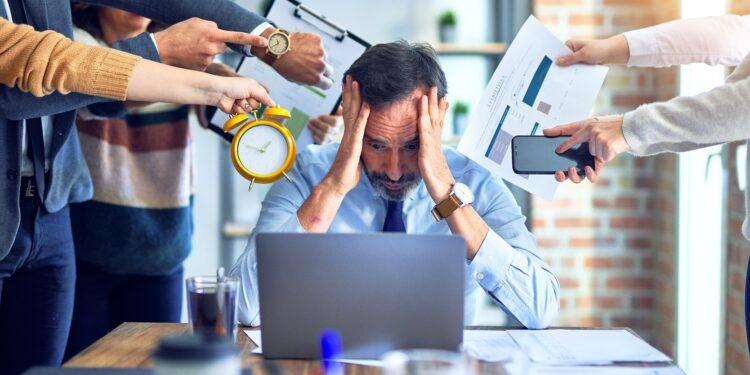 Mann sitzt gestresst vor einem Laptop, während umstehende Personen mit weiteren Aufgaben drängeln.
