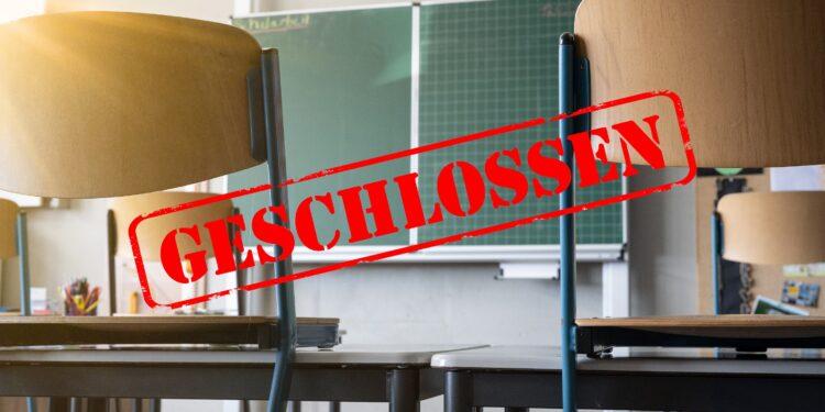"""Klassenzimmer mit Stühlen auf den Tischen und dem Schriftzug """"Geschlossen""""."""