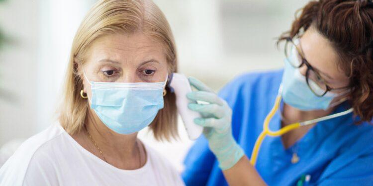 Ärztin mit Maske misst bei einer Frau kit Maske das Fieber im Ohr