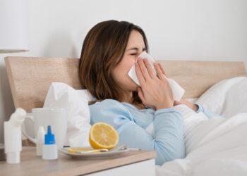 Eine kranke Frau liegt im Bett und schnäuzt sich