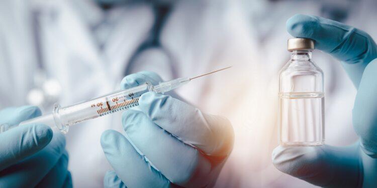 Behandschuhte Hände halten eine Spritze und eine Impfstoffampulle