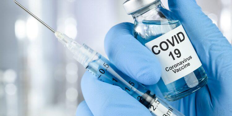 Hand in blauen Handschuhen hält einen COVID-19-Impfstoff und eine Spritze