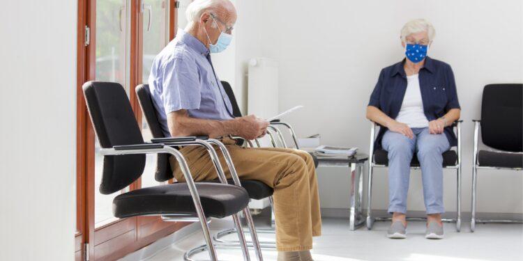 Eine Seniorin und ein Senior mit Mund-Nasen-Bedeckung sitzen in einem Wartezimmer