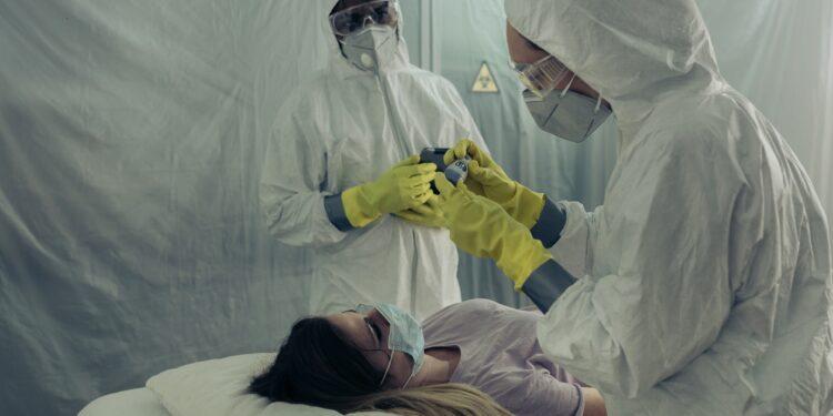 Medizinisches Personal in Schutzanzügen kümmern sich um eine Frau in einem Feldlazarett