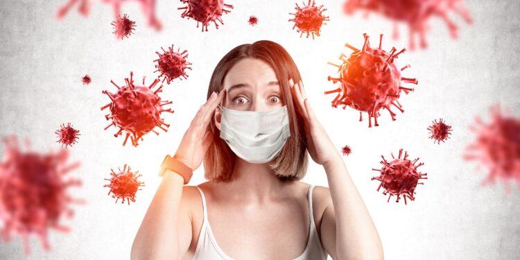 Frau mit Maske schaut ängstlich auf Viren.