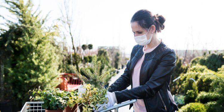 Junge Frau mit Gesichtsmaske beim Einkaufen im Freien eines Gartencenters