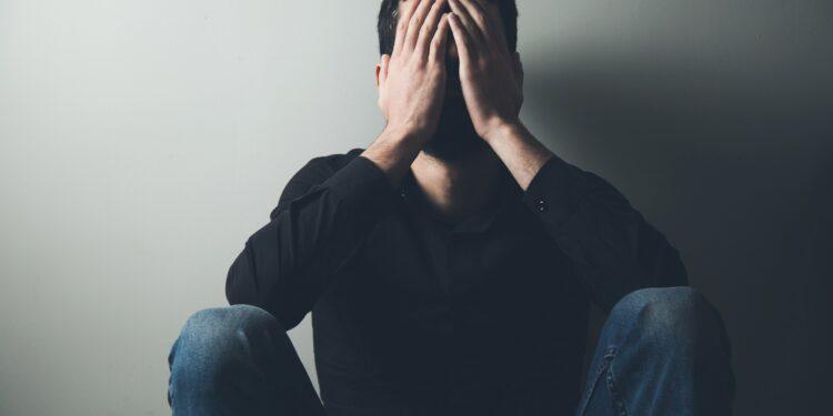 Mann sitzt auf dem Boden und bedeckt das Gesicht mit seinen Händen
