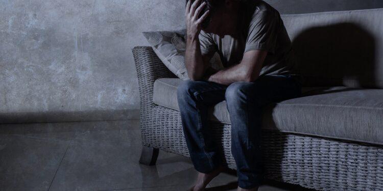 Depressiver Mann sitzt auf Sofa.