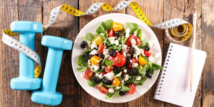 Ein Teller mit Salat, ein Maßband, zwei Hanteln und ein Notizblock mit Stift auf einem Holztisch