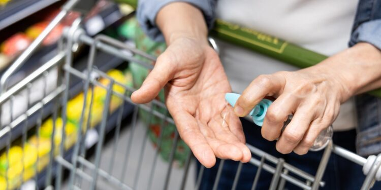 Eine Person beim Einkaufen desinfiziert die Hände mit einem Desinfektionsmittel.