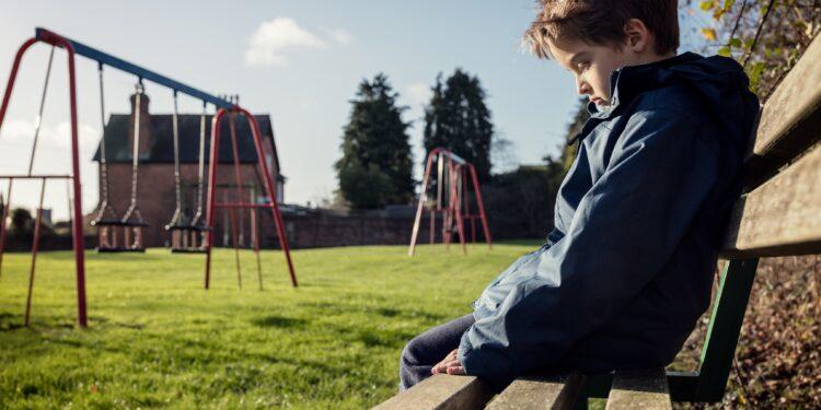 Einsames Kind sitzt im Freien auf einer Bank.