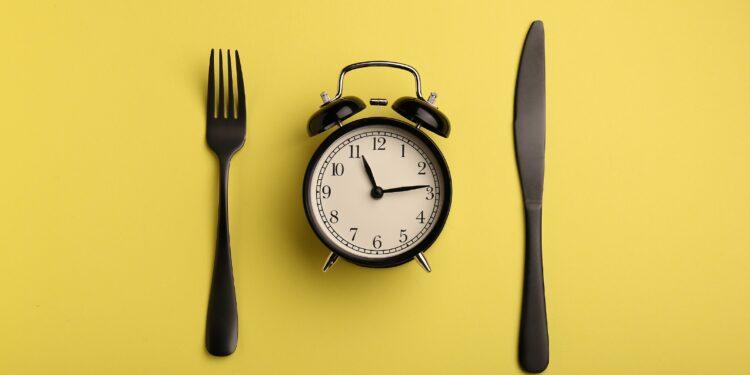 Eine Gabel, ein Wecker und ein Messer auf gelbem Hintergrund