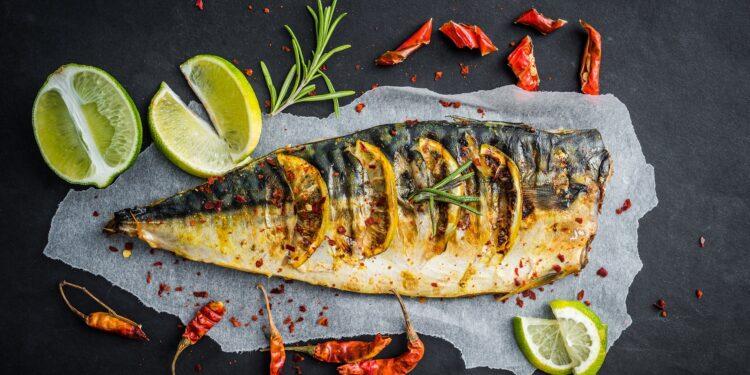 Ein zubereiteter Fisch, umgeben von Limettenscheiben und Gewürzen, liegt auf einer dunklen Oberfläche.