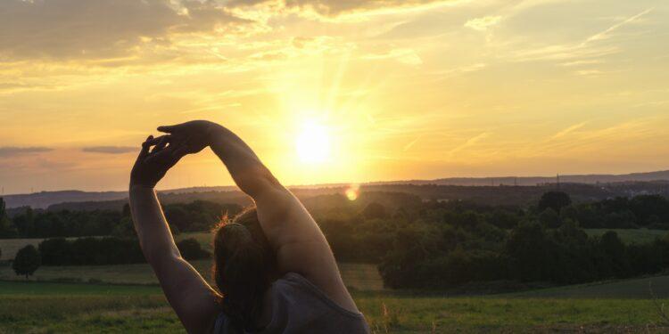 Eine Frau macht Sport bei aufgehender Sonne.
