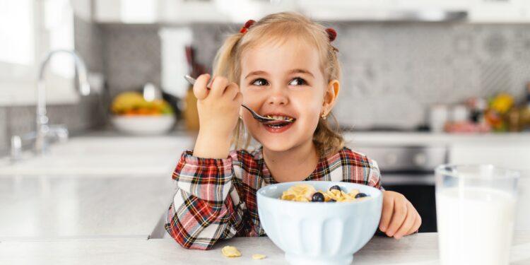 Ein kleines Mädchen, das Frühstück mit Müsli, Milch und Blaubeeren in der Küche isst