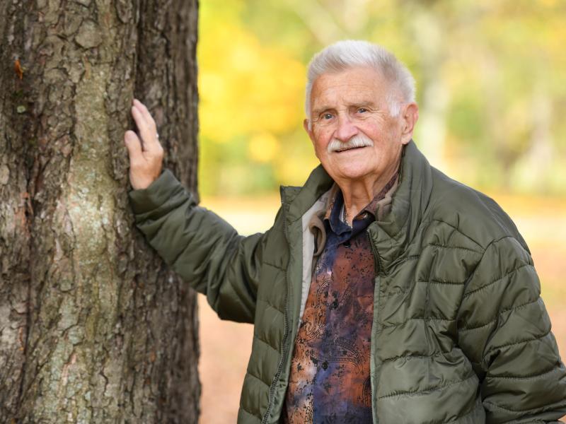 Ein älterer Mann lehnt sich mit der Hand an einen Baum an.