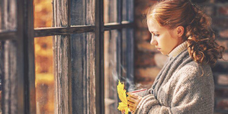 Junge Frau mit einer Tasse in der Hand blickt traurig aus dem Fenster