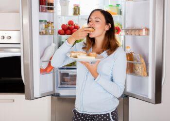 Frau verzehrt Brote vor einem Kühlschrank.