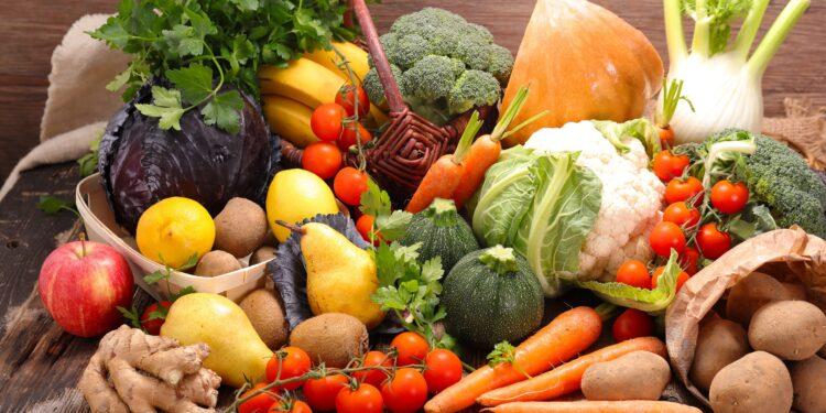 Eine Auswahl an frischem Gemüse und Obst auf einem Holztisch