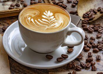 Eine Tasse Cafe Latte mit verziertem Milchschaum neben fischen Kaffeebohnen