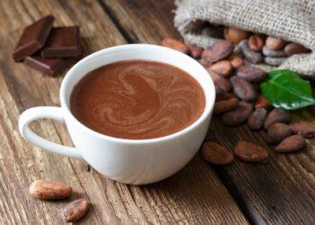 Eine Tasse Kakao steht auf einer hölzernen Oberfläche.