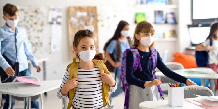 Mehrere Kinder mit Mund-Nasen-Bedeckung in einem Klassenzimmer