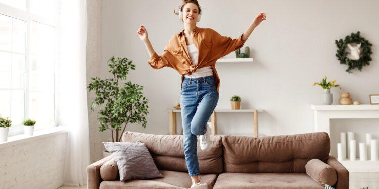 Eine Frau hört Musik und tanzt auf dem Sofa.