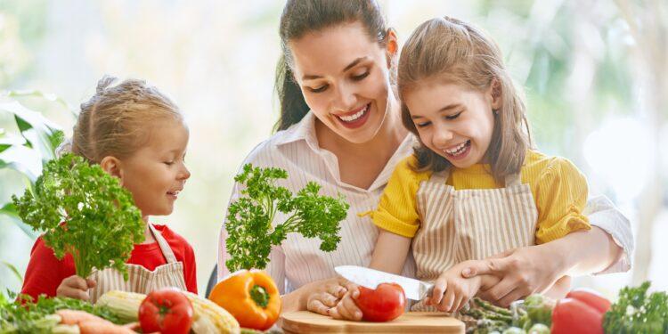 Kinder mit Mutter schneiden Obst und Gemüse.