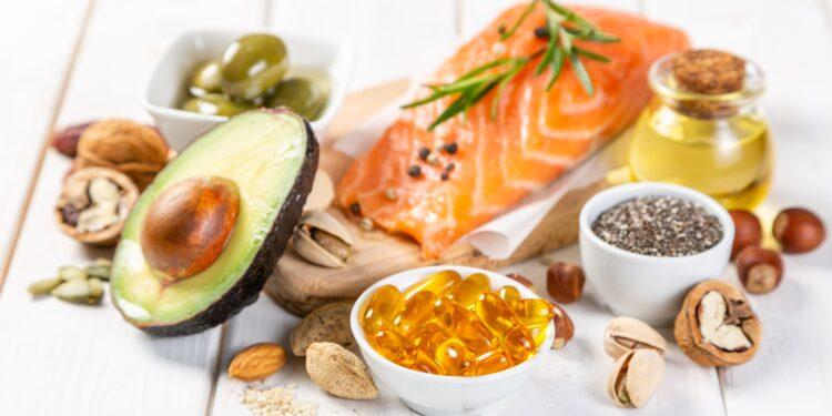 Eine Schale mit Omega-3-Präparaten steht vor gesunden Lebensmitteln, die reich an Omega-3-Fettsäuren sind.