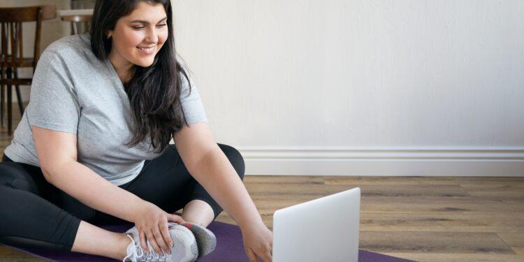 Eine übergewichtige Frau macht Fitness-Übungen vor einem Laptop.
