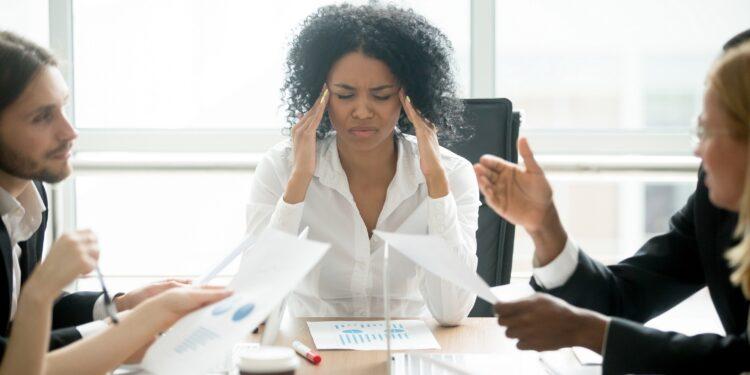 Frau in weißer Bluse leitet ein Meeting und wird von allen Seiten mit Fragen bedrängt sodass sie sich die Schläfen hält