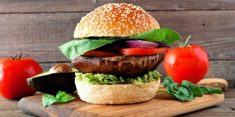 Veganer Burger mit Portobello-Pilz, Avocado, Tomate, Spinat und Zwiebeln auf einem hölzernen Servierbrett