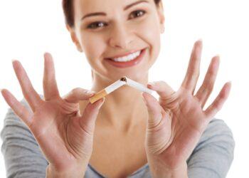 Junge lächelnde Frau bricht eine Zigarette auseinander