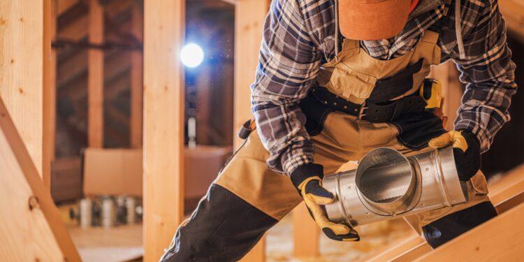 Ein Handwerker beim Bau einer Lüftungsanlage.