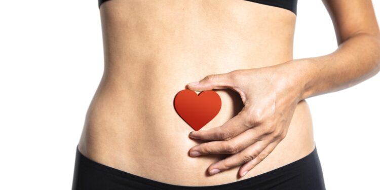 Eine Frau hält ein Herz vor ihren Bauch.