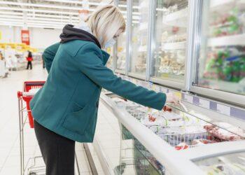 Frau mit Mund-Nasen-Bedeckung holt Ware aus der Tiefkühltruhe im Supermarkt