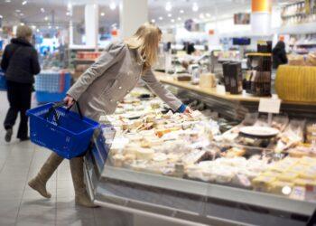 Frau im Supermarkt nimmt sich Käse aus der Selbstbedienungstheke
