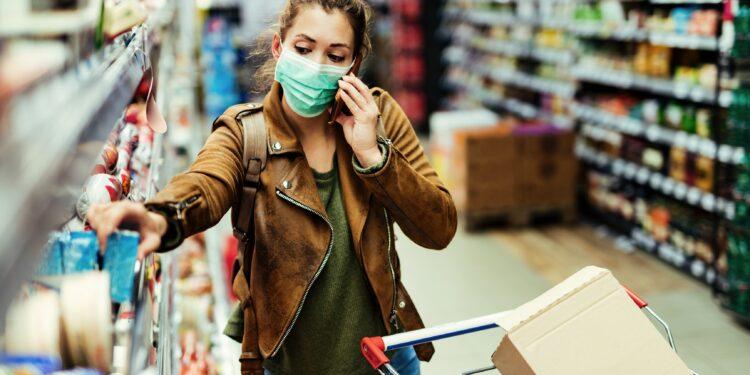 Frau mit Mund-Nasen-Bedeckung telefoniert während des Einkaufens im Supermarkt