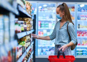 Junge Frau mit Mund-Nasen-Bedeckung beim Einkaufen im Supermarkt