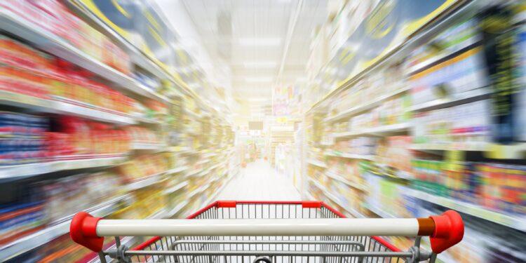 Leerer Einkaufswaagen zwischen Regalen in einem Supermarkt