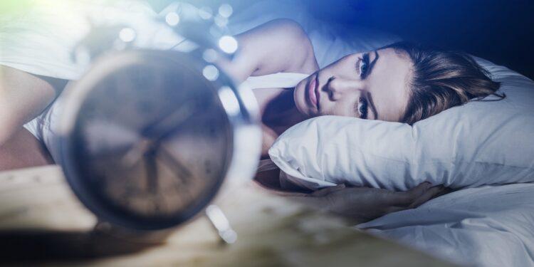 Fraue mit Schlafproblemen schaut auf die Uhr.
