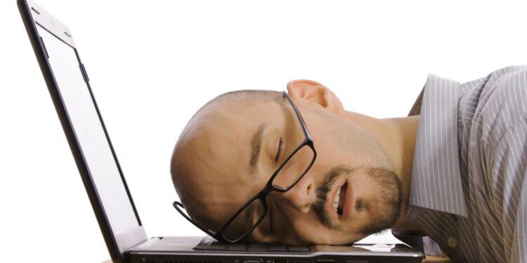 Mann schläft auf seinem Laptop.