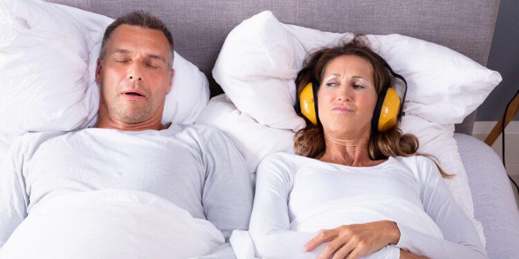 Frau schützt sich mit Kopfhörer vor lautem Schnarchen.