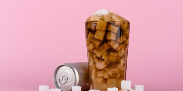 Ein Glas ist voll mit Zuckerwürfeln und einer braunen Flüssigkeit.