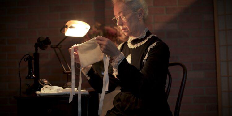 Eine alter Frau näht einen Mundschutz.