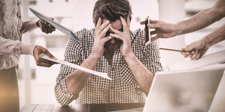 Gestresstem Mann am Schreibtisch werden von mehreren Händen weitere Aufgaben gereicht