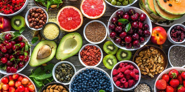 Eine Auswahl an gesunden pflanzlichen Lebensmitteln auf einem Holztisch