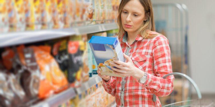 Eine Frau nimmt sich eine Packung mit Müsli aus einem Regal im Supermarkt.