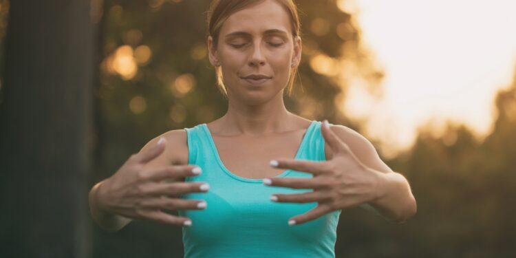 Junge Frau praktiziert Yoga im Freien.